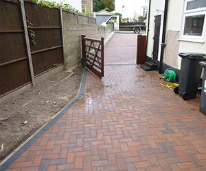 blocked paved driveway down the side of a house with a wooden gate