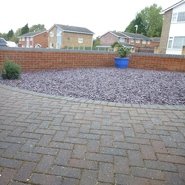 blocked paving with corner filled with stones surround by low brick wall
