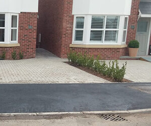dropped kerb with fresh tarmac in front of two houses with block paved and some shrubbery