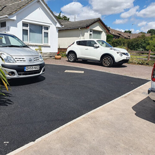 newly tarmaced driveway with cars parked on a sunny day