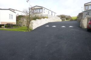fresh tarmac road leading to driveway with speed bump situated between caravans