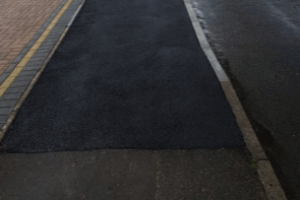 fresh tarmac with dropped kerb with line of hedges leading into road junction