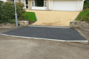 fresh tarmac with dropped kerb in front of gravel driveway and house with double garage