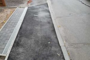 fresh tarmac with dropped kerb adjacent to driveway alongside road with parked cars