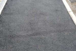 fresh tarmac with dropped kerb showing pavement and junction in road