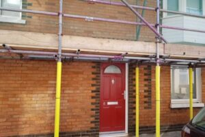 New pointing on brick wall situated under scaffolding at front of a house with a red door