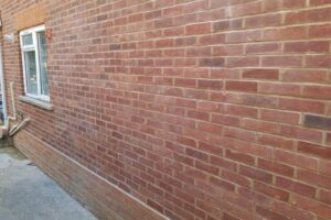 New pointing on brick wall with small window