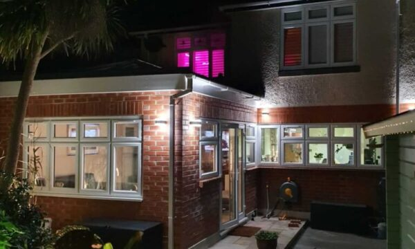 new single story extension in garden of hose with lights on and patio