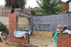 half built brick extension with 3 walls and lots of builders tools