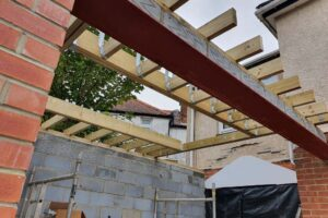 wooden beams for roof from below of brick extension