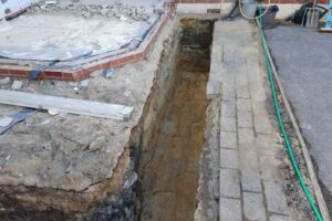 Trench in the ground of back garden in blocked paving