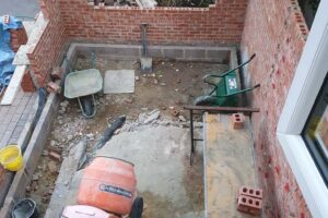view above new extension with newly built walls with work equipment in the middle