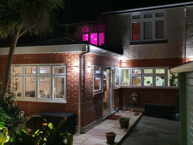 night picture of new extension lit up with wall lights and some brushes and trees