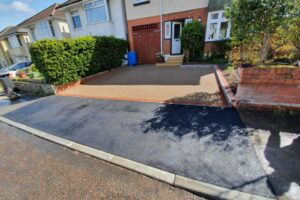 fresh tarmac drop kerb in front of new resin driveway and semi detached house