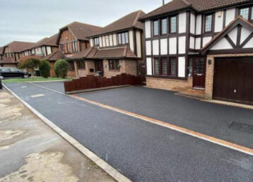long stretch of fresh tarmac dropped kerb in front of tarmac driveway and houses