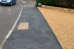 dropped kerb with new tarmac and gravel driveway on the right and road with car driving on the left