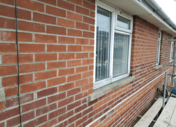 close up of brick wall with window in the middle, picture taken from on top of scaffolding